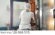 Купить «Female bakes on commercial kitchen - pulls the bread from the oven», видеоролик № 28068515, снято 27 июня 2019 г. (c) Константин Шишкин / Фотобанк Лори
