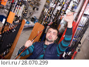 Купить «Young male customer standing with fishing rod in shop», фото № 28070299, снято 16 января 2018 г. (c) Яков Филимонов / Фотобанк Лори