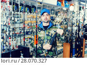 Купить «Male customer in fishing clothing choosing fishing rod», фото № 28070327, снято 16 января 2018 г. (c) Яков Филимонов / Фотобанк Лори