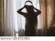 Купить «Silhouette of teenager girl wearing headphones in front of the window», фото № 28073083, снято 23 февраля 2018 г. (c) Константин Шишкин / Фотобанк Лори