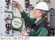 """Пожилой электрик вешает табличку """"Работать здесь"""" на электрический силовой щиток. Стоковое фото, фотограф Кекяляйнен Андрей / Фотобанк Лори"""