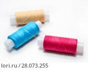 Купить «Три катушки с разноцветными нитками для шитья на белом фоне», фото № 28073255, снято 10 ноября 2011 г. (c) Кекяляйнен Андрей / Фотобанк Лори