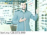 Купить «young male seller assisting woman in choosing door handles in shop», фото № 28073999, снято 5 апреля 2017 г. (c) Яков Филимонов / Фотобанк Лори