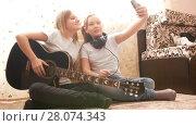 Купить «Two female teens making selfie and posing with musical instruments sitting on the floor at home», видеоролик № 28074343, снято 20 марта 2018 г. (c) Константин Шишкин / Фотобанк Лори