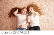 Two teen girls lying on the floor, laughing and making selfie the phone, their hair spread over the floor. Стоковое видео, видеограф Константин Шишкин / Фотобанк Лори
