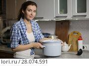 Купить «young woman in the kitchen prepares a meal», фото № 28074591, снято 24 января 2018 г. (c) Типляшина Евгения / Фотобанк Лори