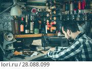 Купить «male worker sewing stitches on belt in leather workshop», фото № 28088099, снято 22 марта 2019 г. (c) Яков Филимонов / Фотобанк Лори
