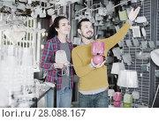 Купить «Man showing interesting options for home lamps», фото № 28088167, снято 16 февраля 2017 г. (c) Яков Филимонов / Фотобанк Лори