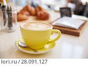 Купить «Large cappuccino coffee in yellow cup and saucer on counter», фото № 28091127, снято 31 августа 2016 г. (c) easy Fotostock / Фотобанк Лори