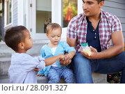 Купить «Father Giving Children Candy On Steps Outside Hose», фото № 28091327, снято 1 сентября 2016 г. (c) easy Fotostock / Фотобанк Лори