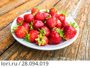 Fresh red strawberries in a white bowl standing on the rustic wooden table. Стоковое фото, фотограф FotograFF / Фотобанк Лори