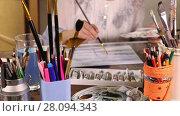 Купить «Woman painting with watercolors in art studio with brushes in foreground», видеоролик № 28094343, снято 22 января 2016 г. (c) Алексей Кузнецов / Фотобанк Лори