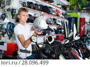 Купить «Man sitting and choosing helmet for motorcycle», фото № 28096499, снято 17 июля 2017 г. (c) Яков Филимонов / Фотобанк Лори