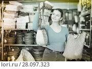 Купить «Young woman standing with wicker bag», фото № 28097323, снято 13 декабря 2017 г. (c) Яков Филимонов / Фотобанк Лори