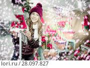 Купить «Woman choosing Christmas decoration at market», фото № 28097827, снято 22 декабря 2016 г. (c) Яков Филимонов / Фотобанк Лори