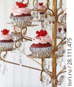 Купить «Red Velvet cupcakes displayed on a chandelier.», фото № 28111475, снято 6 января 2018 г. (c) easy Fotostock / Фотобанк Лори