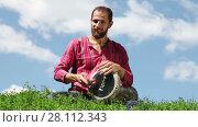 Купить «Young Caucasian man sitting on the green grass and playing the drum on blue sky background. Audio included», видеоролик № 28112343, снято 6 августа 2015 г. (c) Алексей Кузнецов / Фотобанк Лори