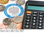 Рублевые монеты, банкноты и калькулятор лежат на письме от налоговой, рядом с эмблемой федеральной налоговой службы (крупным планом) Стоковое фото, фотограф E. O. / Фотобанк Лори