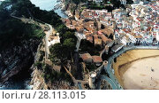 Купить «Aerial view of picturesque rocky landscape with fortified walls and residential buildings of Tossa de Mar, Spain», видеоролик № 28113015, снято 12 февраля 2018 г. (c) Яков Филимонов / Фотобанк Лори