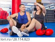 Купить «Female boxer is sitting with man and talking about healthy in gym.», фото № 28114823, снято 21 августа 2017 г. (c) Яков Филимонов / Фотобанк Лори