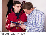 Купить «Man is writing documents about deliver order by courier», фото № 28114879, снято 5 февраля 2018 г. (c) Яков Филимонов / Фотобанк Лори