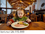 Купить «Little girl is having breakfast sitting at wooden table in spacious room», фото № 28115999, снято 4 февраля 2017 г. (c) Losevsky Pavel / Фотобанк Лори