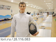 Купить «Man in costume with helmet stands in gym for fencing training, other people out of focus», фото № 28116083, снято 9 февраля 2017 г. (c) Losevsky Pavel / Фотобанк Лори