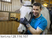 Купить «Handsome man in gloves stands with white horse in harness and smiles in stable», фото № 28116107, снято 17 февраля 2017 г. (c) Losevsky Pavel / Фотобанк Лори