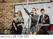 Купить «Two women sing and two men play music ob stage during perfrom», фото № 28116123, снято 18 февраля 2017 г. (c) Losevsky Pavel / Фотобанк Лори