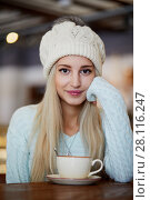 Купить «Young smiling blonde woman in knitted hat with fur pompom sits in cafeteria at table with cup of coffee», фото № 28116247, снято 1 ноября 2016 г. (c) Losevsky Pavel / Фотобанк Лори