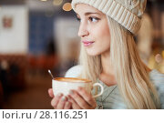 Купить «Young blonde woman in knitted hat holds cup of coffee in hands», фото № 28116251, снято 1 ноября 2016 г. (c) Losevsky Pavel / Фотобанк Лори