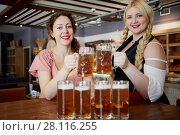 Купить «Two smiling women clang glass mugs with beer above table», фото № 28116255, снято 1 ноября 2016 г. (c) Losevsky Pavel / Фотобанк Лори