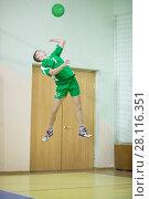 Купить «Man in green sport uniform jumps and hits ball during volleyball game in gym», фото № 28116351, снято 8 ноября 2016 г. (c) Losevsky Pavel / Фотобанк Лори