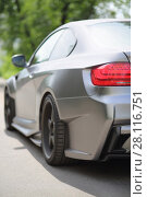Купить «MOSCOW - JUN 19, 2016: Silver stylish car on road in front of green foliage, back view», фото № 28116751, снято 19 июня 2016 г. (c) Losevsky Pavel / Фотобанк Лори