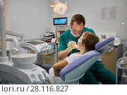 Купить «MOSCOW, RUSSIA - OCT 19, 2016: Dentist examines mouth and teeth of boy sitting in armchair in Children Medical Center Sanare for children of all ages from birth to 17 years old», фото № 28116827, снято 19 октября 2016 г. (c) Losevsky Pavel / Фотобанк Лори