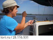 Купить «Boy teenager in cap controls boat during sailing on river at summer day», фото № 28116931, снято 19 августа 2016 г. (c) Losevsky Pavel / Фотобанк Лори