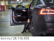 Купить «Rear view of modern car with open driver door and leg and arm of woman comes out», фото № 28116935, снято 11 ноября 2015 г. (c) Losevsky Pavel / Фотобанк Лори