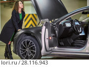 Купить «MOSCOW, RUSSIA - NOV 11, 2015: Young woman (with model release) examines inner surface of hood of the Tesla S car. The Tesla Model S produced by Tesla Motors, and introduced in June 2012.», фото № 28116943, снято 11 ноября 2015 г. (c) Losevsky Pavel / Фотобанк Лори