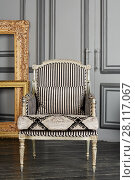 Купить «Silvery armchair and golden frames in room with grey walls and black floor», фото № 28117067, снято 14 ноября 2015 г. (c) Losevsky Pavel / Фотобанк Лори