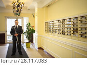Handsome man in a business suit and tie holds a silver umbrella in the hallway near the mailboxes. Стоковое фото, фотограф Losevsky Pavel / Фотобанк Лори