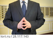 Купить «A man in a business suit joined fingers with each other in front of the mailboxes», фото № 28117143, снято 21 февраля 2016 г. (c) Losevsky Pavel / Фотобанк Лори