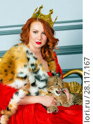Купить «Red-haired woman in red dress, cloak and with crown on head sits on couch holding lynx cub», фото № 28117167, снято 14 ноября 2015 г. (c) Losevsky Pavel / Фотобанк Лори