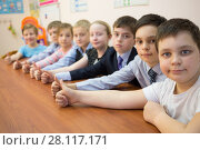 Купить «Eight children are thumbs-up and sitting at the table», фото № 28117171, снято 28 апреля 2015 г. (c) Losevsky Pavel / Фотобанк Лори