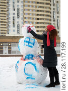 Купить «Young woman paints body of snowman with aerosol spray in courtyard of residential buildings», фото № 28117199, снято 23 февраля 2016 г. (c) Losevsky Pavel / Фотобанк Лори
