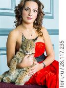 Купить «Woman in red dress sits on couch holding lynx cub», фото № 28117235, снято 14 ноября 2015 г. (c) Losevsky Pavel / Фотобанк Лори