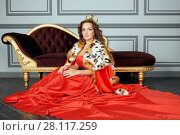 Купить «Woman in red dress, cloak and with crown on head sits on floor near couch in room», фото № 28117259, снято 14 ноября 2015 г. (c) Losevsky Pavel / Фотобанк Лори