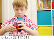 Купить «MOSCOW - MAY 7, 2016: Boy (with MR) plays with Rubik Cube. Over 350 million cubes sold worldwide making it world top-selling puzzle game and the world best-selling toy», фото № 28117311, снято 7 мая 2016 г. (c) Losevsky Pavel / Фотобанк Лори