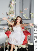Купить «Woman in white dress sits in armchair at room under money banknotes shower», фото № 28117351, снято 14 ноября 2015 г. (c) Losevsky Pavel / Фотобанк Лори