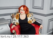 Купить «Red-haired woman in black dress anf fur mantle sits in red armchair in room», фото № 28117363, снято 14 ноября 2015 г. (c) Losevsky Pavel / Фотобанк Лори