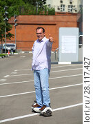 Купить «Happy man thumbs up on GyroScooter on street at sunny summer day», фото № 28117427, снято 25 июня 2016 г. (c) Losevsky Pavel / Фотобанк Лори